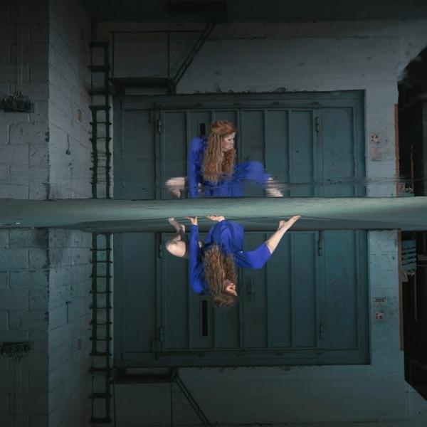 Kvinne med rødt langt hår som sitter på huk med ene foten strekt frem. Skikkelsen hennes speiles i et vannspeil på gulvet.