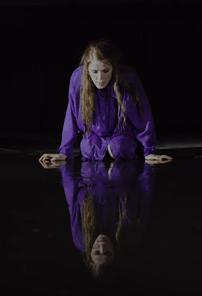 kvinne i et mørkt rom. Hun sitter på kne og kikker på sitt eget speilbilde i et vannspeil. Hun har langt røst hår og har på sen en lilla skjortekjole.