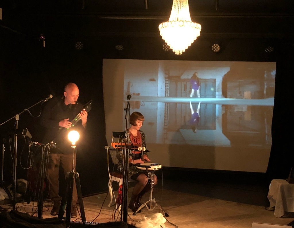 Man and woman playing instruments. Video on large screen in the background.